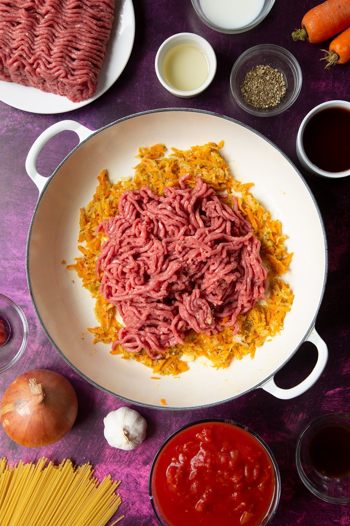 A large frying pan with fried carrot, onion, garlic and dried oregano. Raw lean beef mince has been added. Ingredients to make spaghetti bolognese Gordon Ramsay style surround the pan.