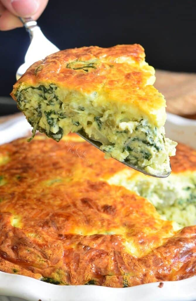 A slice of Spinach Artichoke Crustless Quiche being picked up using a serving fork. The remainder of the quiche is seen below the slice inside a dish.