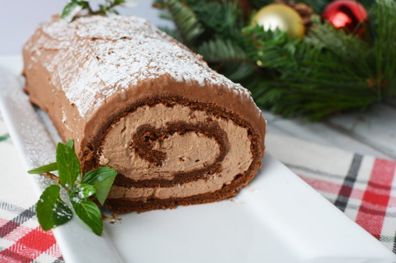 Large yule log cake sitting on a long rectangular plate with a red, white and black checked tea towel underneeth. In the background there's some foliage with christmas baubles.