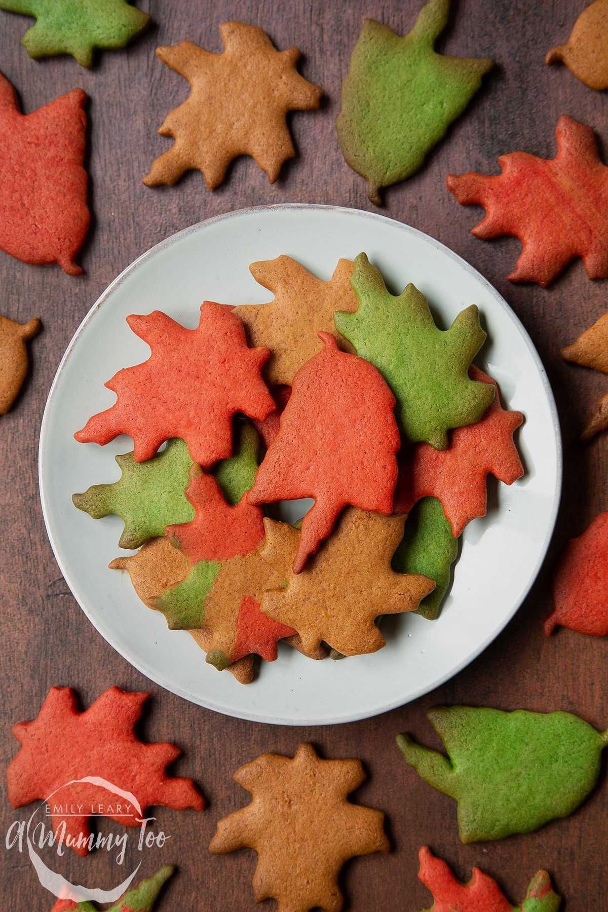 A plate of colourful red, green and brown autumn cookies cut into the shapes of autumn leaves. A red leaf biscuit sits in the centre.
