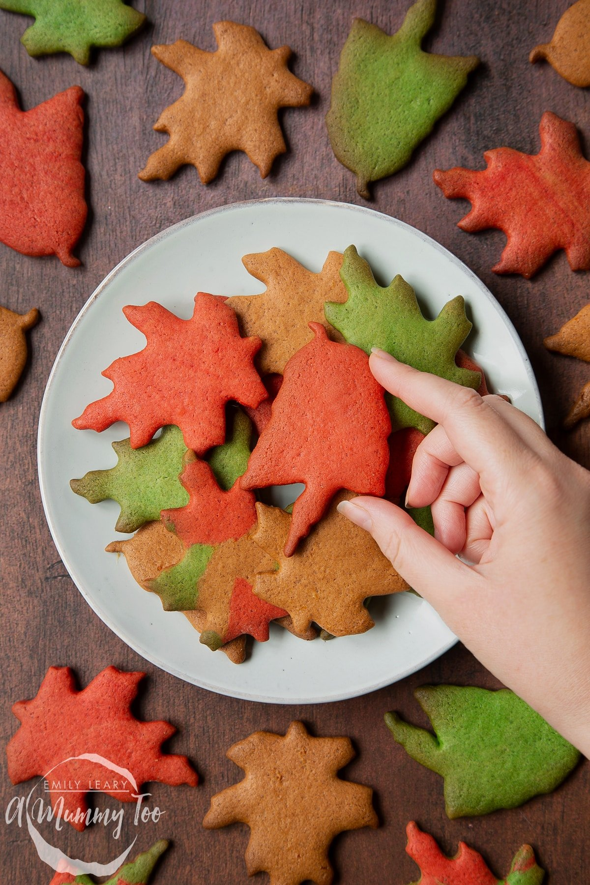 A plate of colourful red, green and brown autumn cookies cut into the shapes of autumn leaves. A hands reaches for a red one.