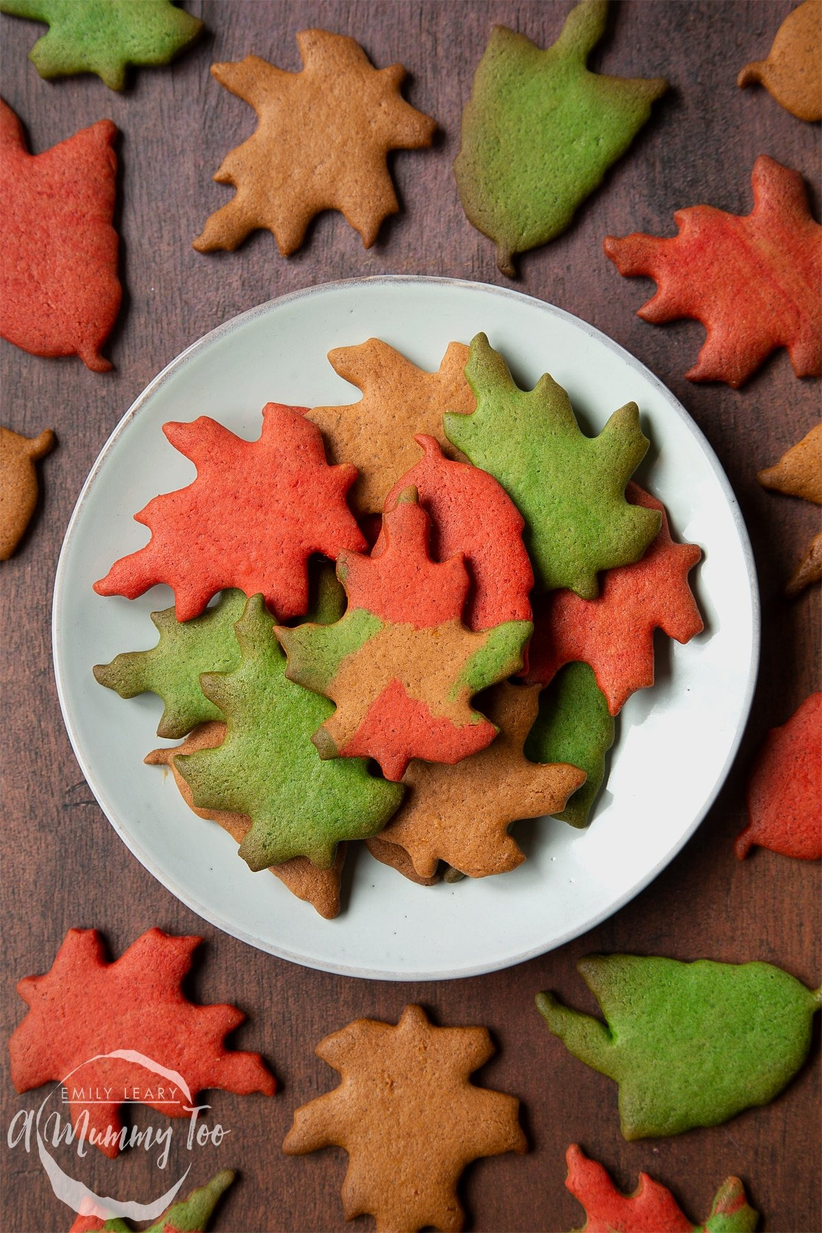 A plate of colourful red, green and brown autumn cookies cut into the shapes of autumn leaves. More Autumn biscuits are arranged on the wooden surface surrounding the plate.