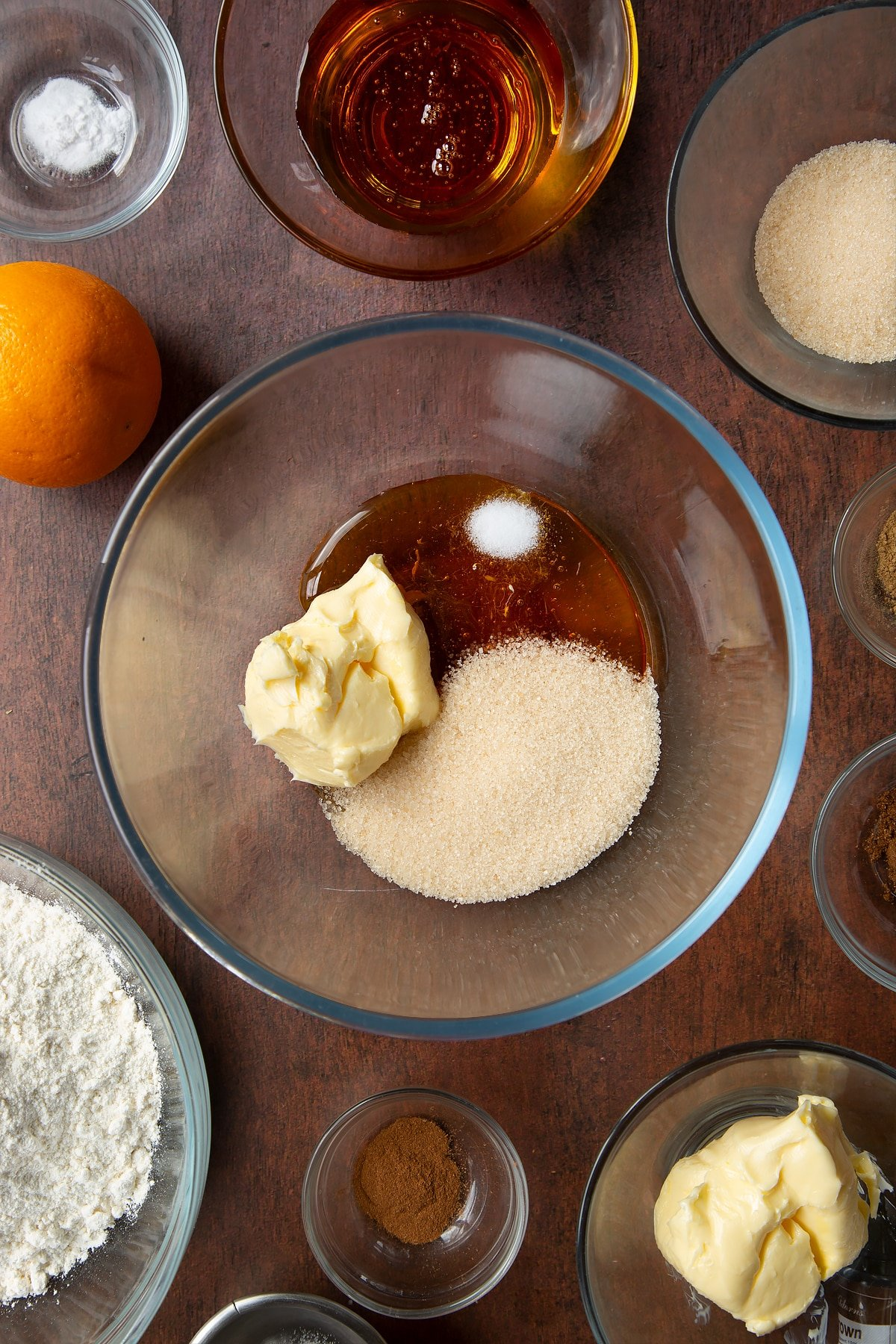 Butter, sugar, salt and golden syrup in a bowl. Ingredients to make autumn cookies surround the bowl.