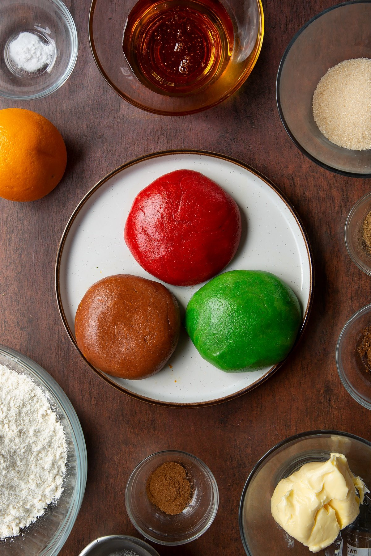 Three balls of coloured and spiced cookie dough on a plate. Ingredients to make autumn cookies surround the plate.