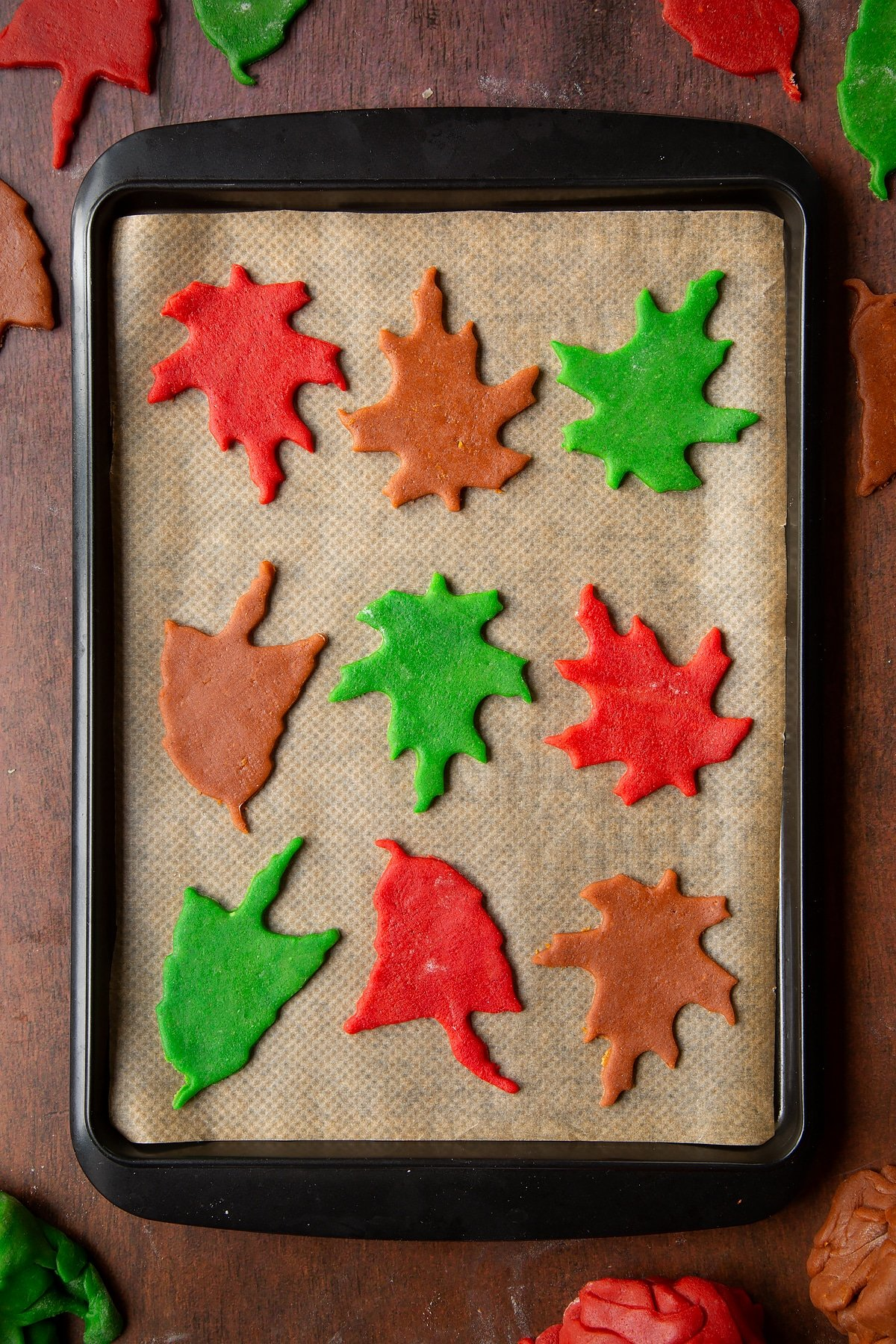 Autumn leaf cookies ready to bake on a tray lined with baking paper.