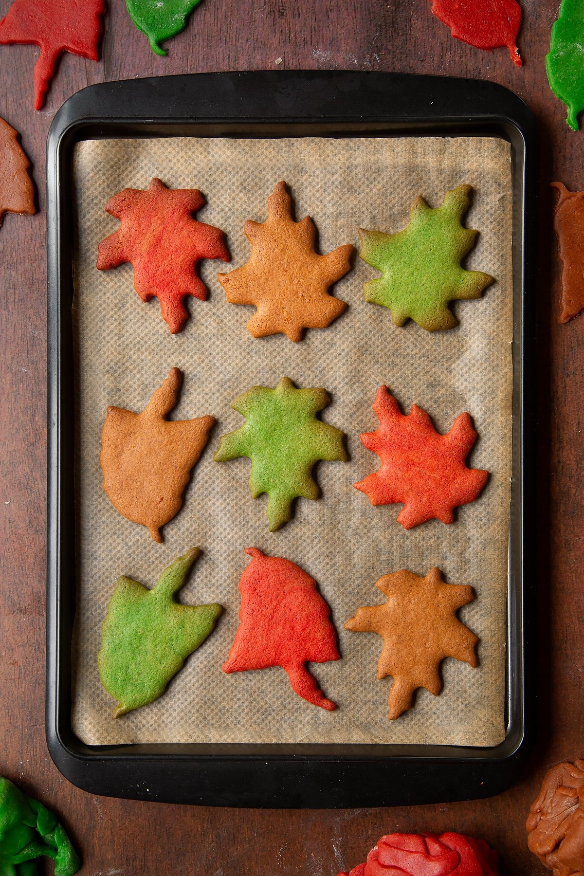 Autumn leaf cookies cooling on a tray lined with baking paper.