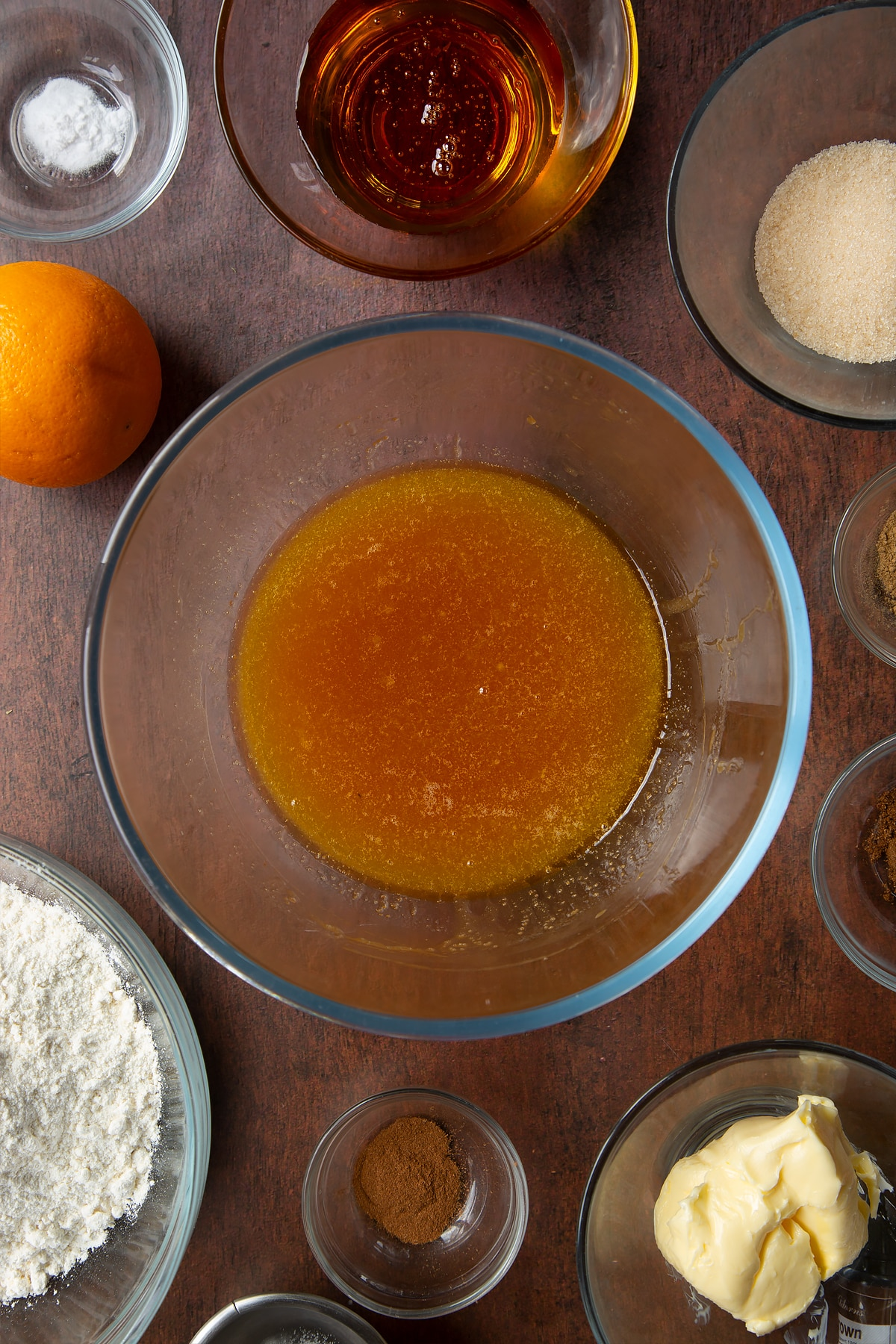 Melted butter, sugar and golden syrup in a bowl. Ingredients to make autumn cookies surround the bowl.