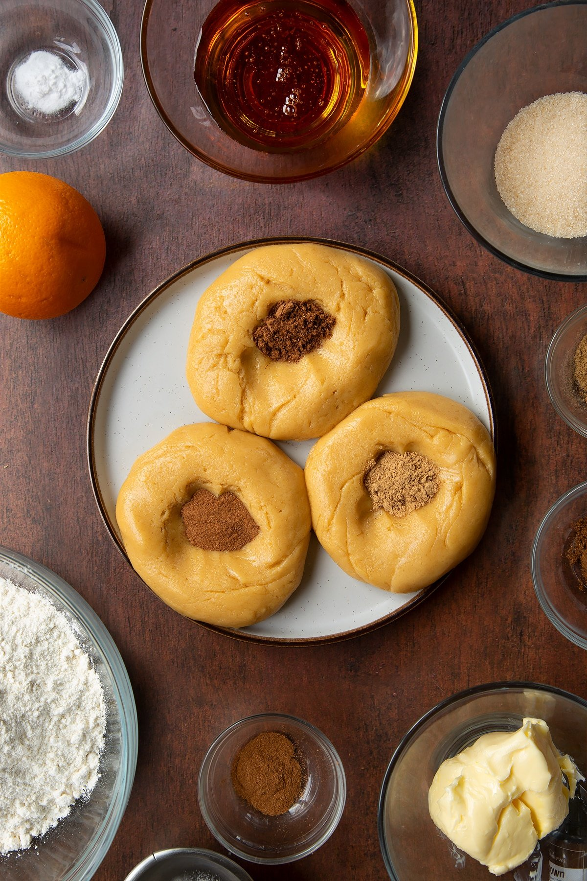 Three balls of cookie dough on a plate with spices on top of them. Ingredients to make autumn cookies surround the plate.