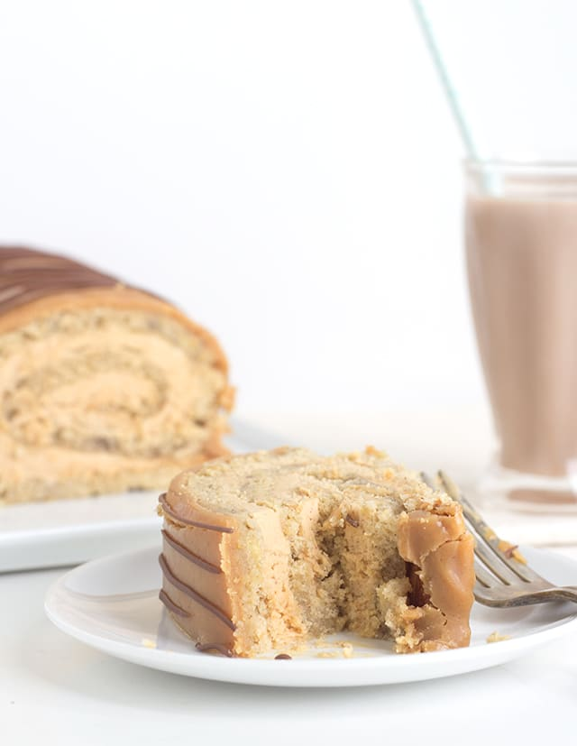 A slice of Banana Roll Cake With Whipped Peanut Butter Ganache  sits on a white plate with a fork on the side. In the background there's a milkshake.