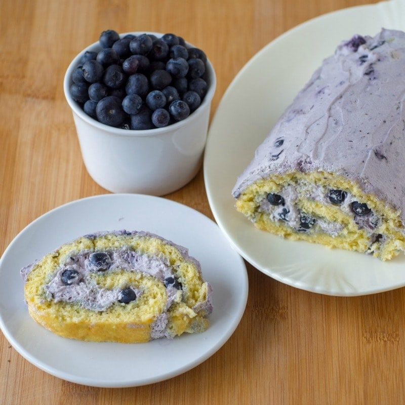 Blueberry Swiss roll cake with the main cake sitting on a large decorative plate and a slice placed on white circular plate with a cup of blueberries at the side. All sitting ontop of a wooden surface.