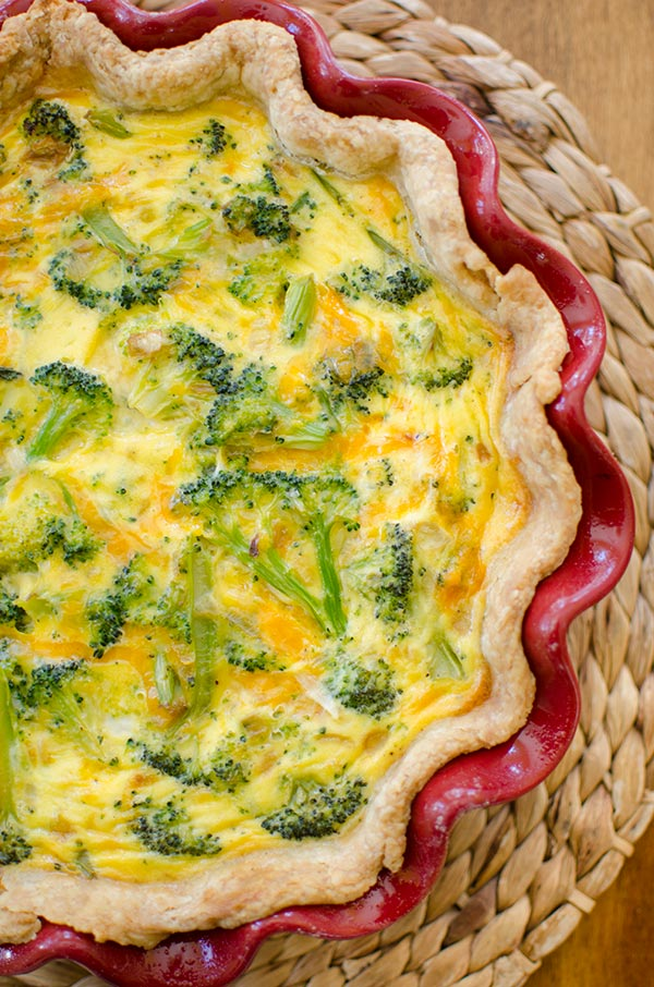 Broccoli Cheddar Quiche inside a red decorative dish ontop of a wicker placemat. The quiche image is positioned on the lefthandside and is cut off.