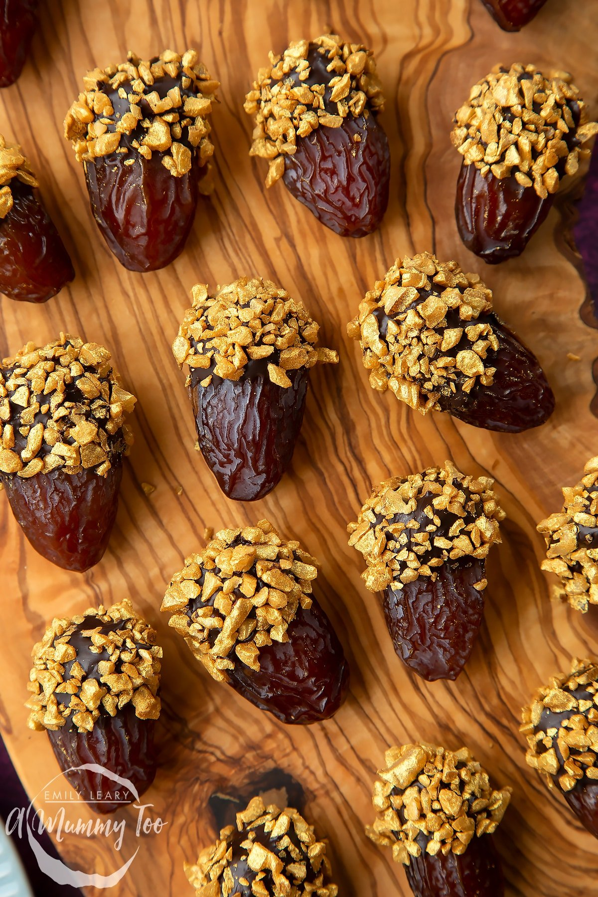 Close up of medjool dates dipped in chocolate. The chocolate dates are on a wooden board and have be studded with gold chopped nuts.