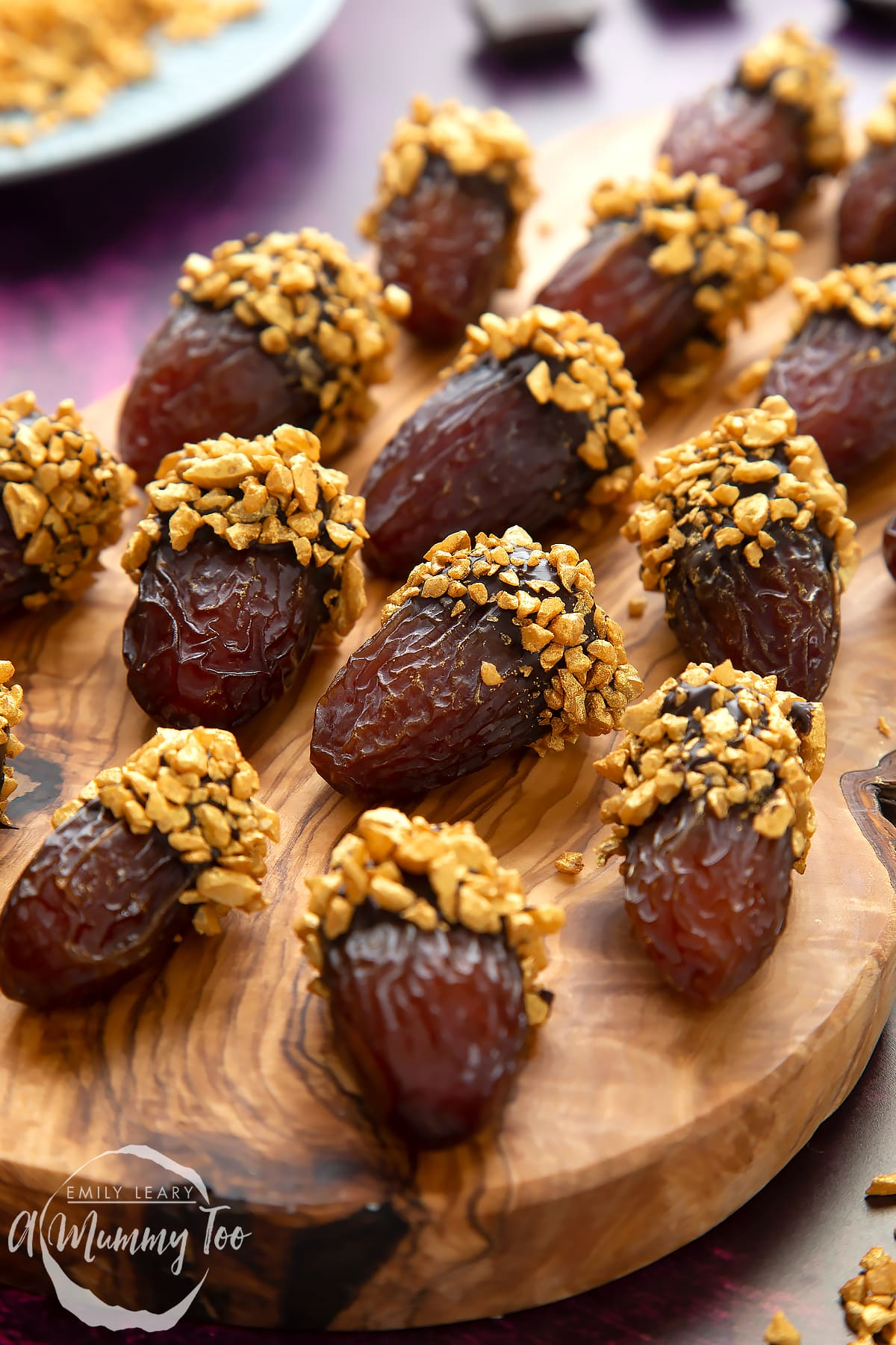 Medjool dates dipped in chocolate. The chocolate dates are on a wooden board and have be studded with gold chopped nuts.