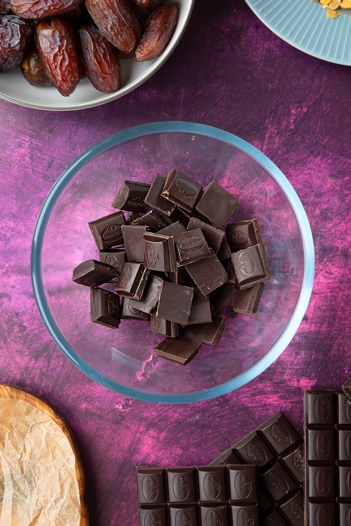 Dark chocolate squares in a bowl, surrounded by ingredients to make chocolate dates.