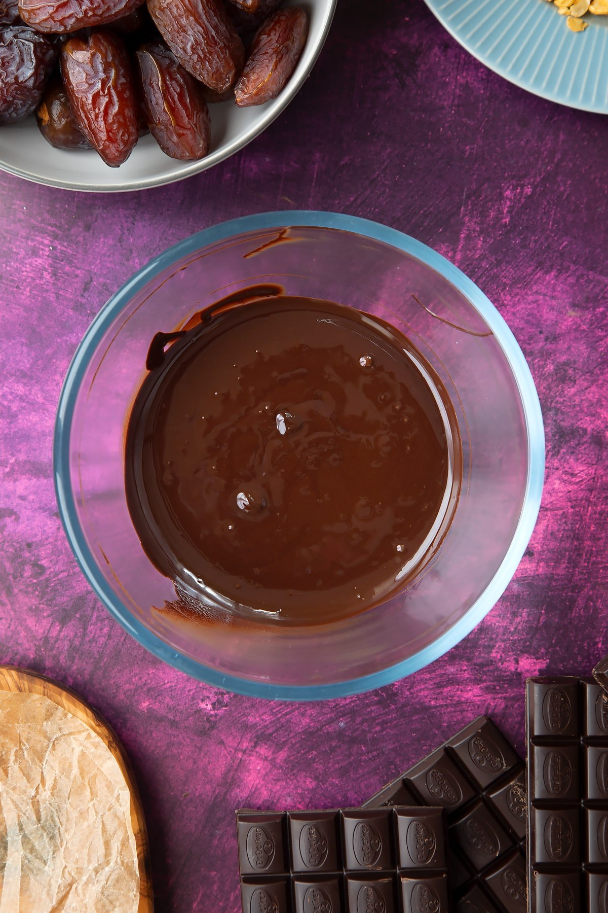 Melted chocolate in a bowl, surrounded by ingredients to make chocolate dates.