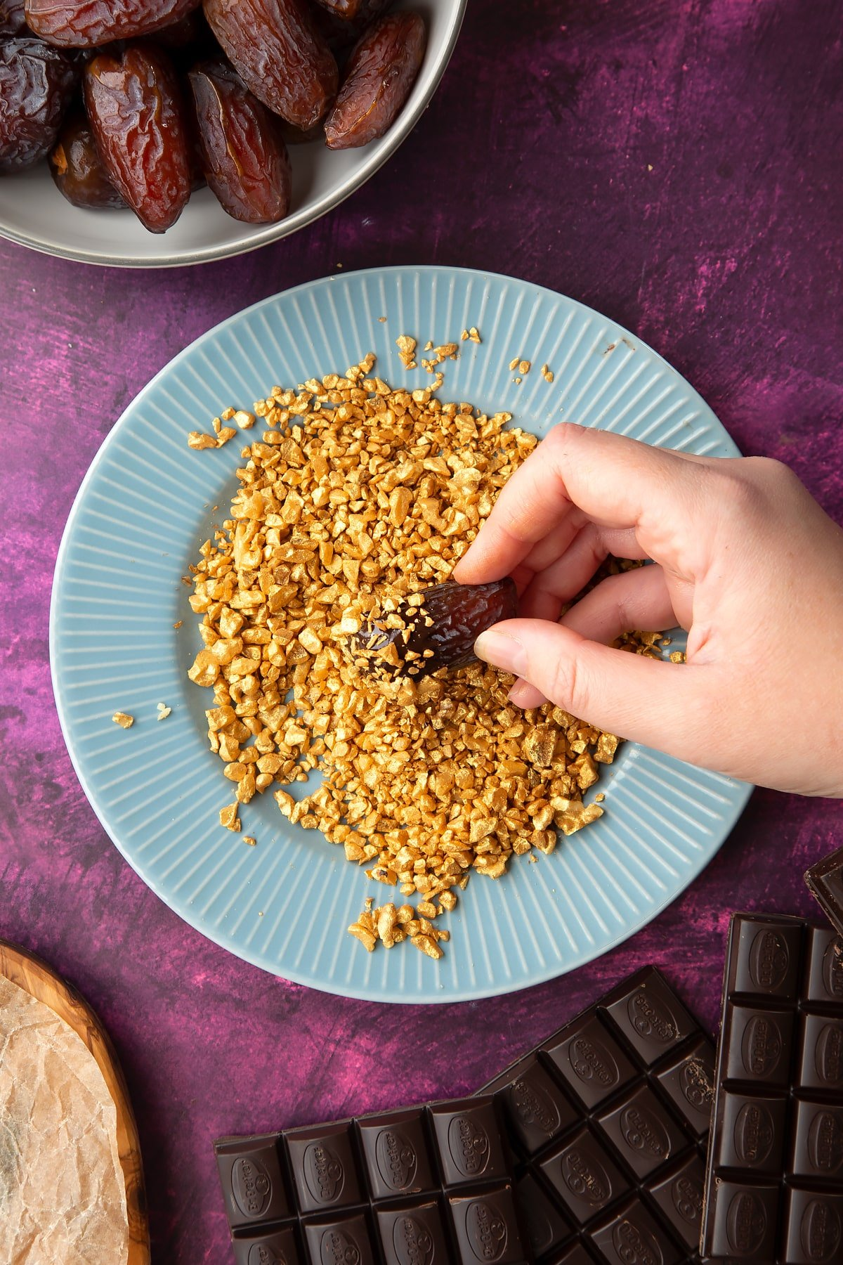 Chopped walnuts sprayed gold on a blue plate, surrounded by ingredients to make chocolate dates. A hand holds a chocolate and nut coated date.