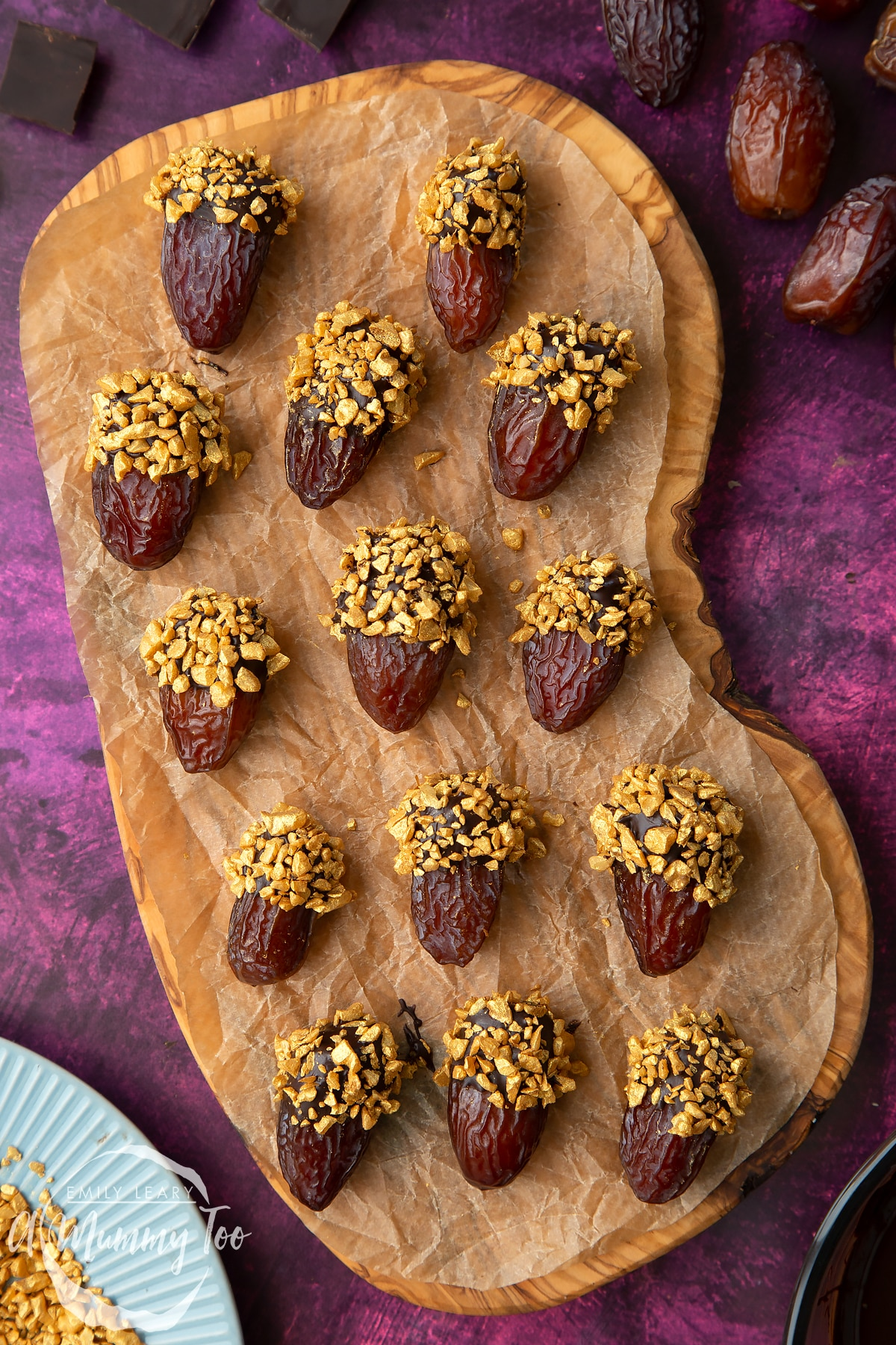 Medjool dates dipped in chocolate. The chocolate dates are on a wooden board lined with brown baking paper. The dates have be studded with gold chopped nuts. Nuts and chocolate surround the board.