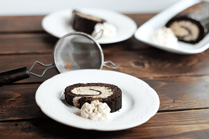 A wooden table has two plates with a slice of chocolate rolled cake with cookie dough. In the background you can see a rectangular plate with the remainder of the chocolate rolled cake.