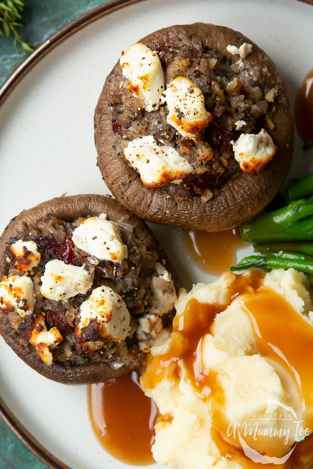 Overhead shot of crispy stuffed mushrooms topped with goats cheese and mashed potato on the side served on a white plate with a mummy too logo in the lower-right corner
