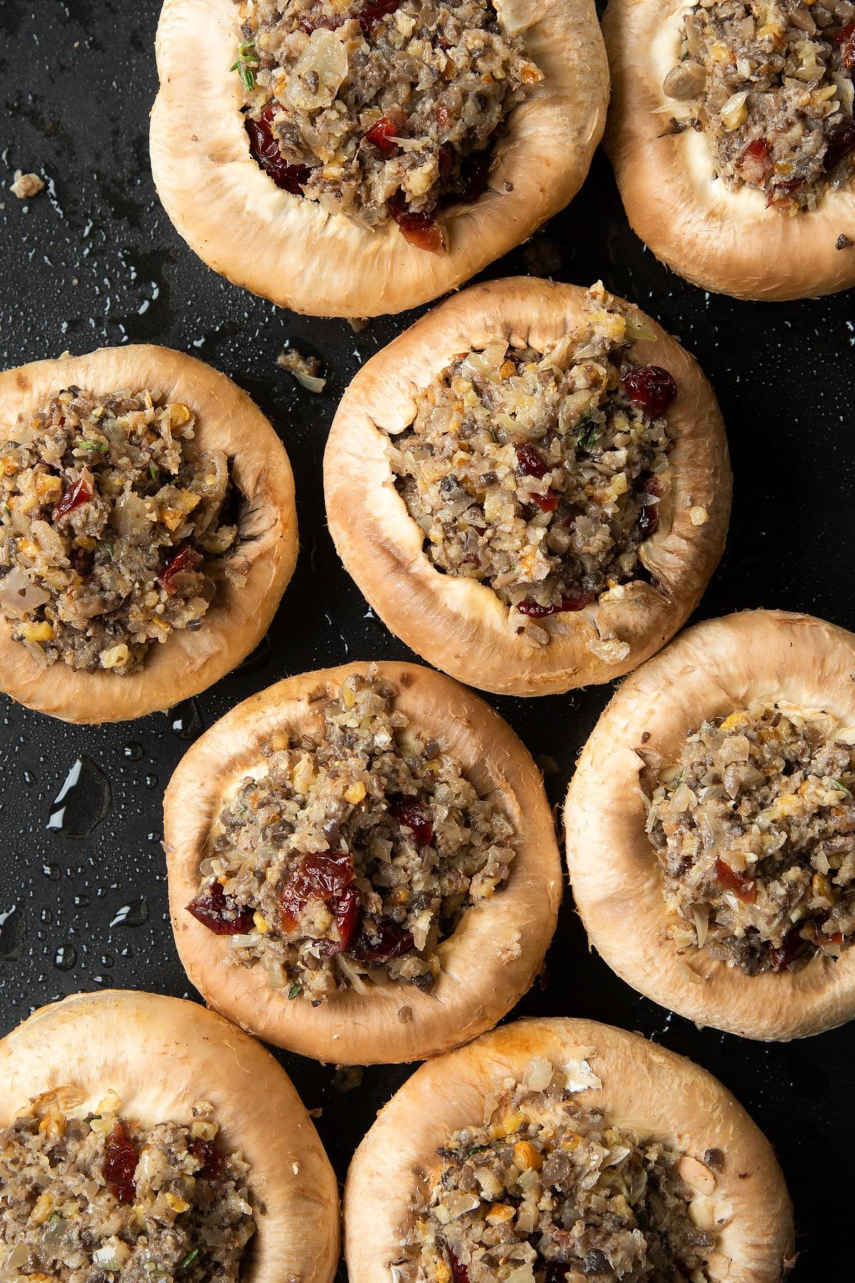 Overhead shot of filling inside mushrooms on a baking tray