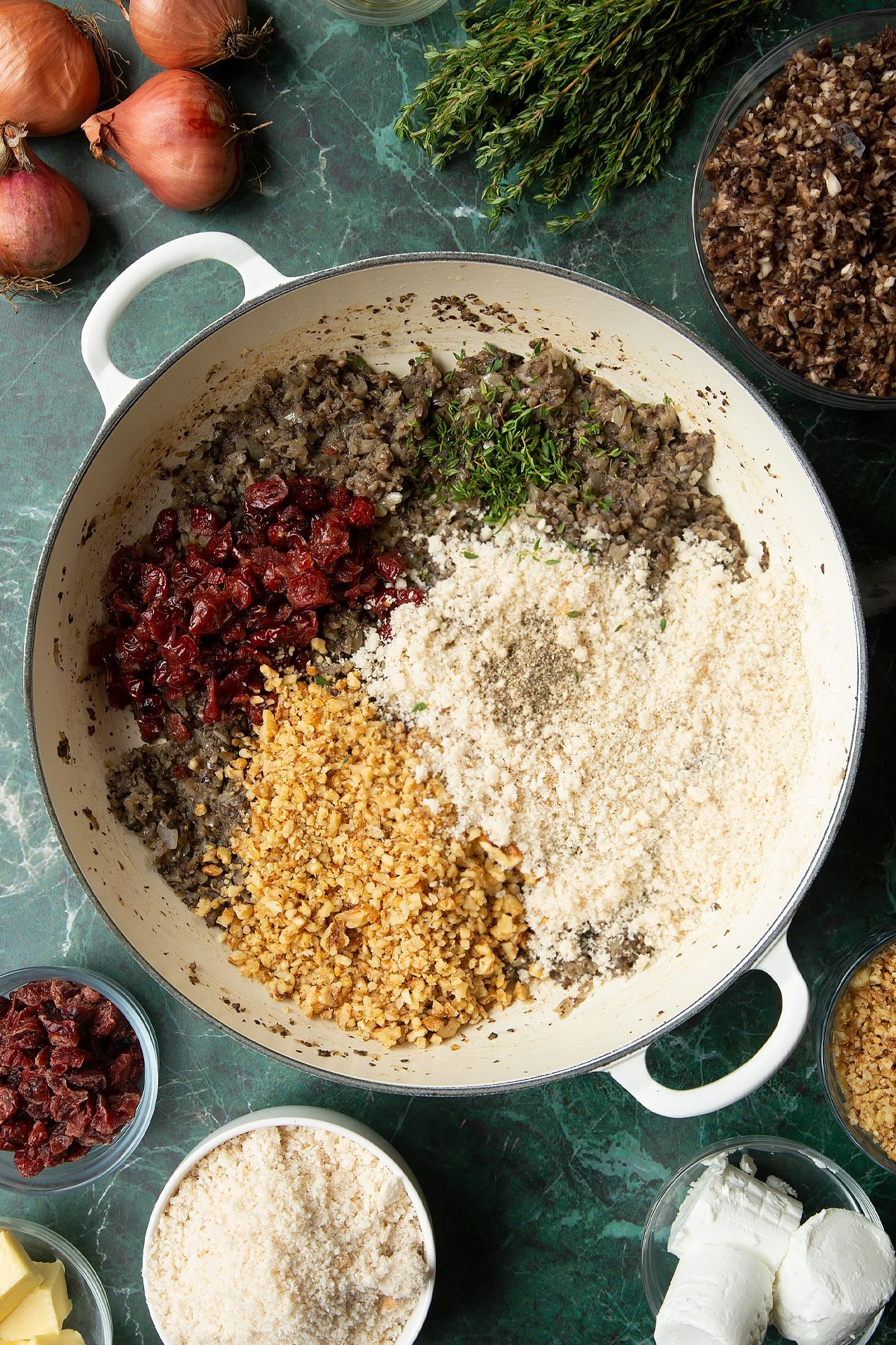 Overhead shot of cranberries, cooked mushrooms, walnuts, thyme, and breadcrumbs in a large frying pan