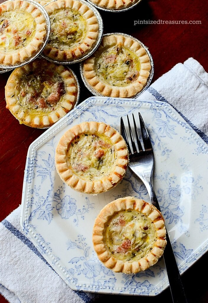 Two Ham & Havarti Mini Quiches sit on a decorative blue and white plate with a fork at the side. In the top right of the image there's a stack of additional miniture Ham & Havarti Mini Quiches.