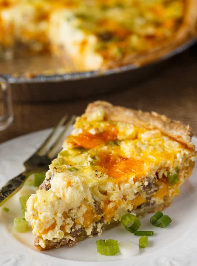 A Hamburger Quiche slice on a white plate with a fork at the side. The quiche slice is decorated with finely chopped chives. In the background you can see the full quiche sitting in a pie tin.