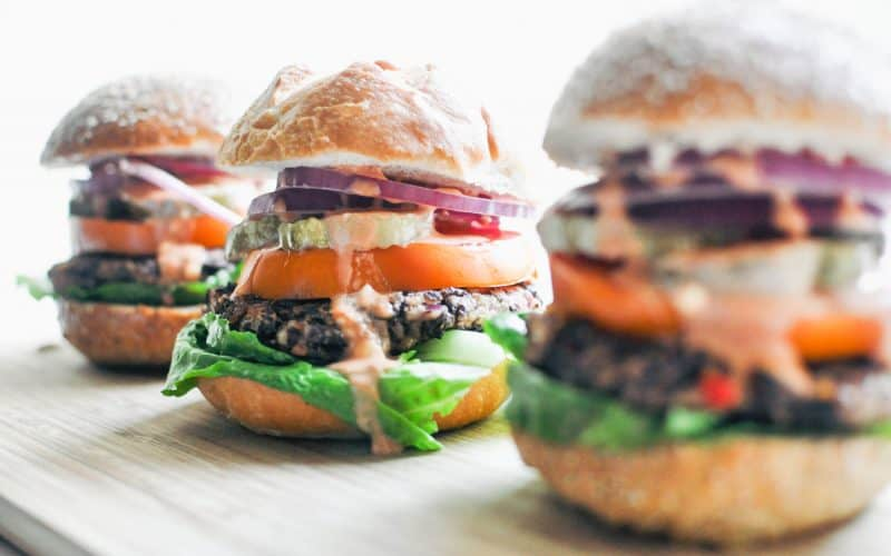 Three black bean burgers lined up on a wooden surface. The middle burger is the one most in focus.