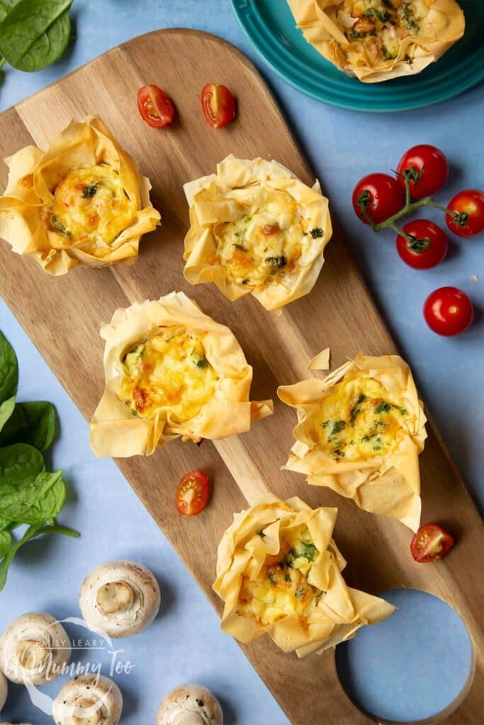 Four Filo Pastry Mini Quiches laid on a wooden chopping board on a light blue background. At the side there's a vine of cherry tomatoes and a blue plate with another mini quiche.
