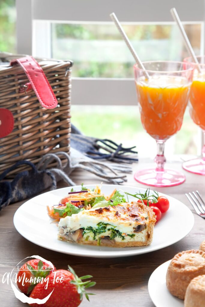 A slice of Chestnut Mushroom, Spinach & Feta Quiche sits on a white plate with a side salad and some on the vine tomatoes. At the front of the image you can see some pork pies on a plate and some strawberries and in the background a picnic basket and two drinks.