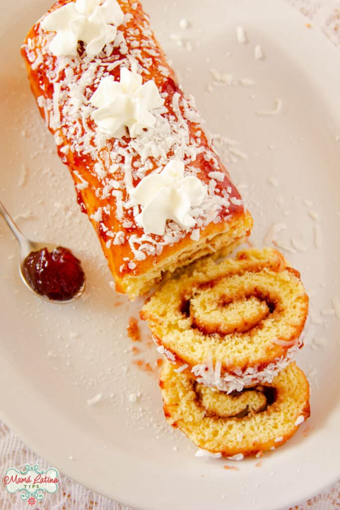 Mexican jelly roll overhead shot with one slice cut off and a spoon full of jelly at the side.