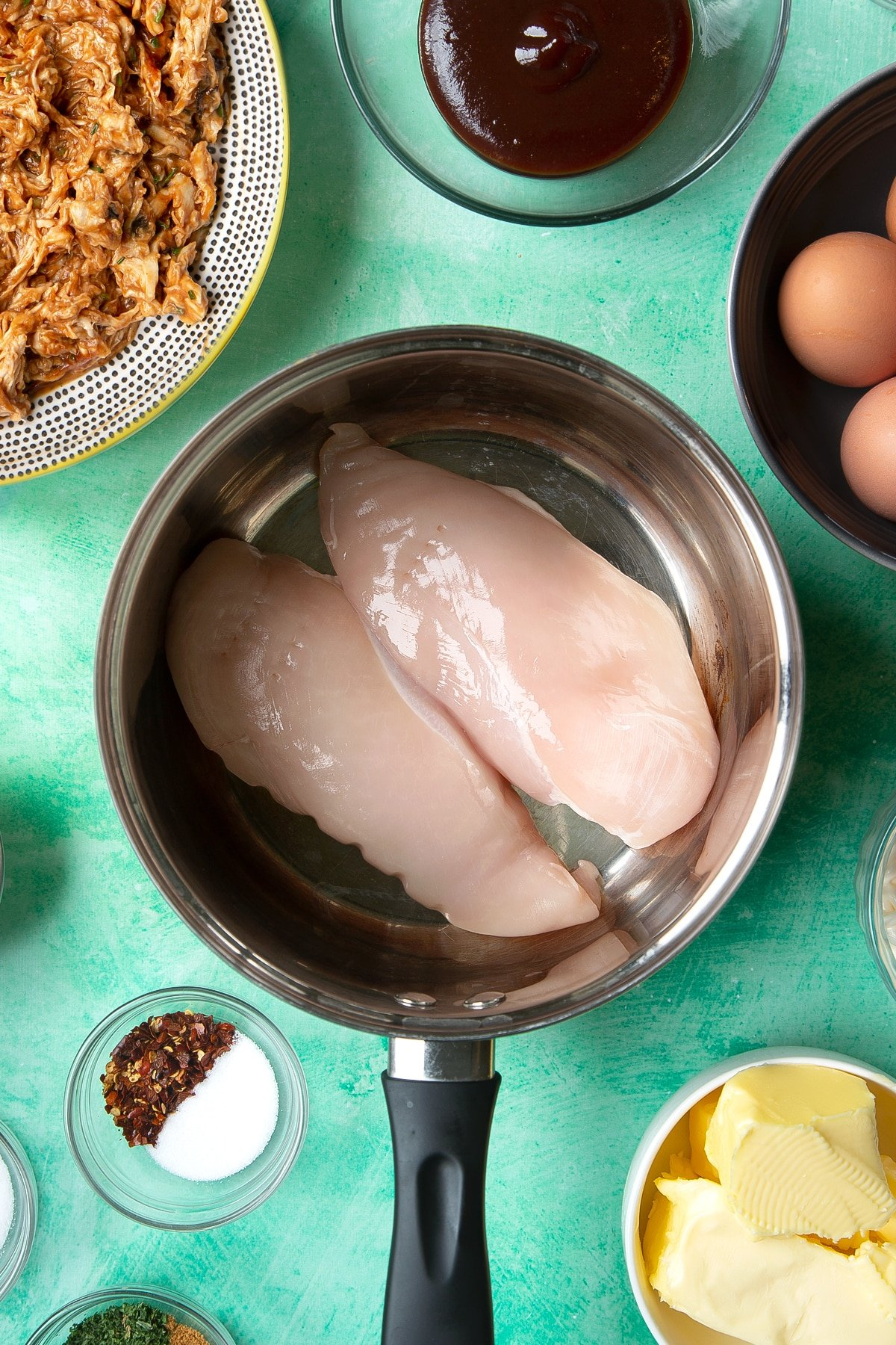 Two raw chicken breasts in a pan. Ingredients to make chicken doughnuts surround the pan.