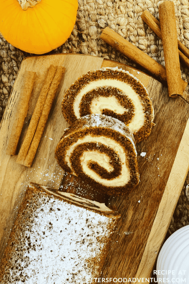 A pumpkin roll with two slices cut off. Cinemon sticks decorate the side of the wooden chopping board next to the roll.