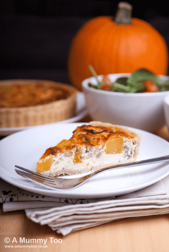 Roast Pumpkin & Caramelised Onion Quiche slice sits on a white plate in the foreground with a fork at the side. The plate sits on a handful of napkins. In the background there's a bowl of salad and a whole pumpkin.