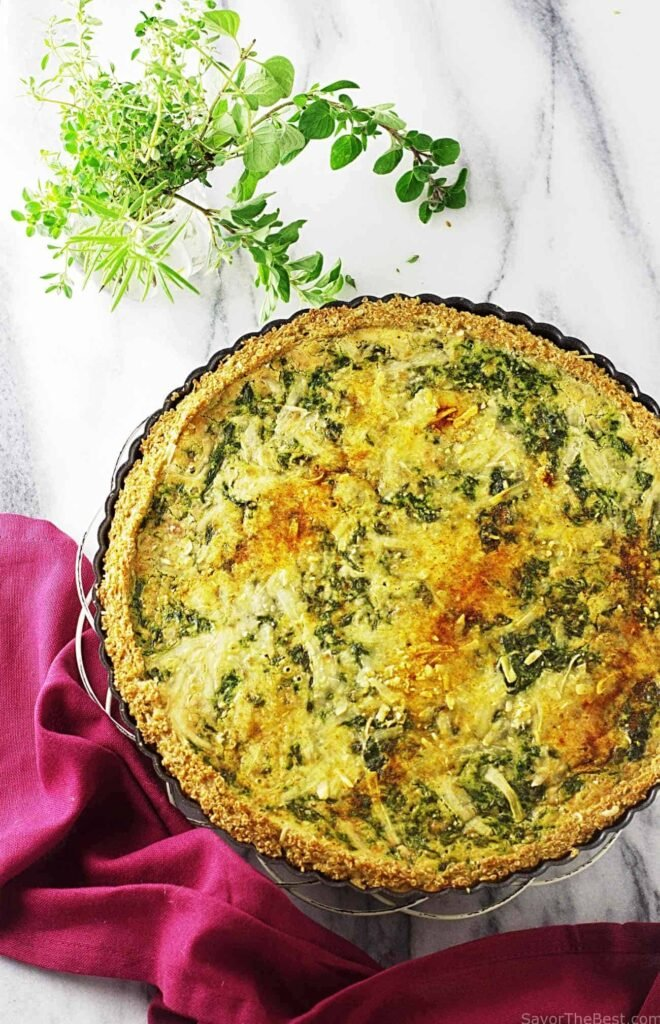 A large Spinach-Gouda Quiche With Quinoa Crust sits on a white marble background, at the side there's some leaves and a red napkin.