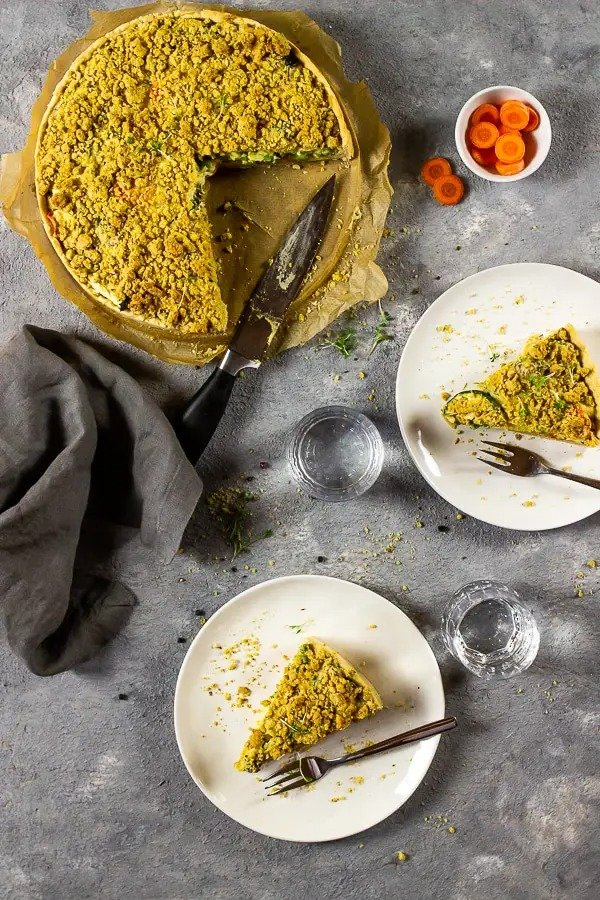A large Garden Veggie Quiche With Cheesy Crumbs with two slices cut out. Both of the slices are situated on a white plate with a fork at the side.