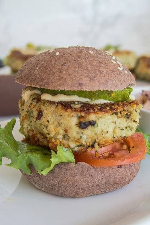 Keto cauliflower falafel burger on a white plate filled with lettuace and tomato.