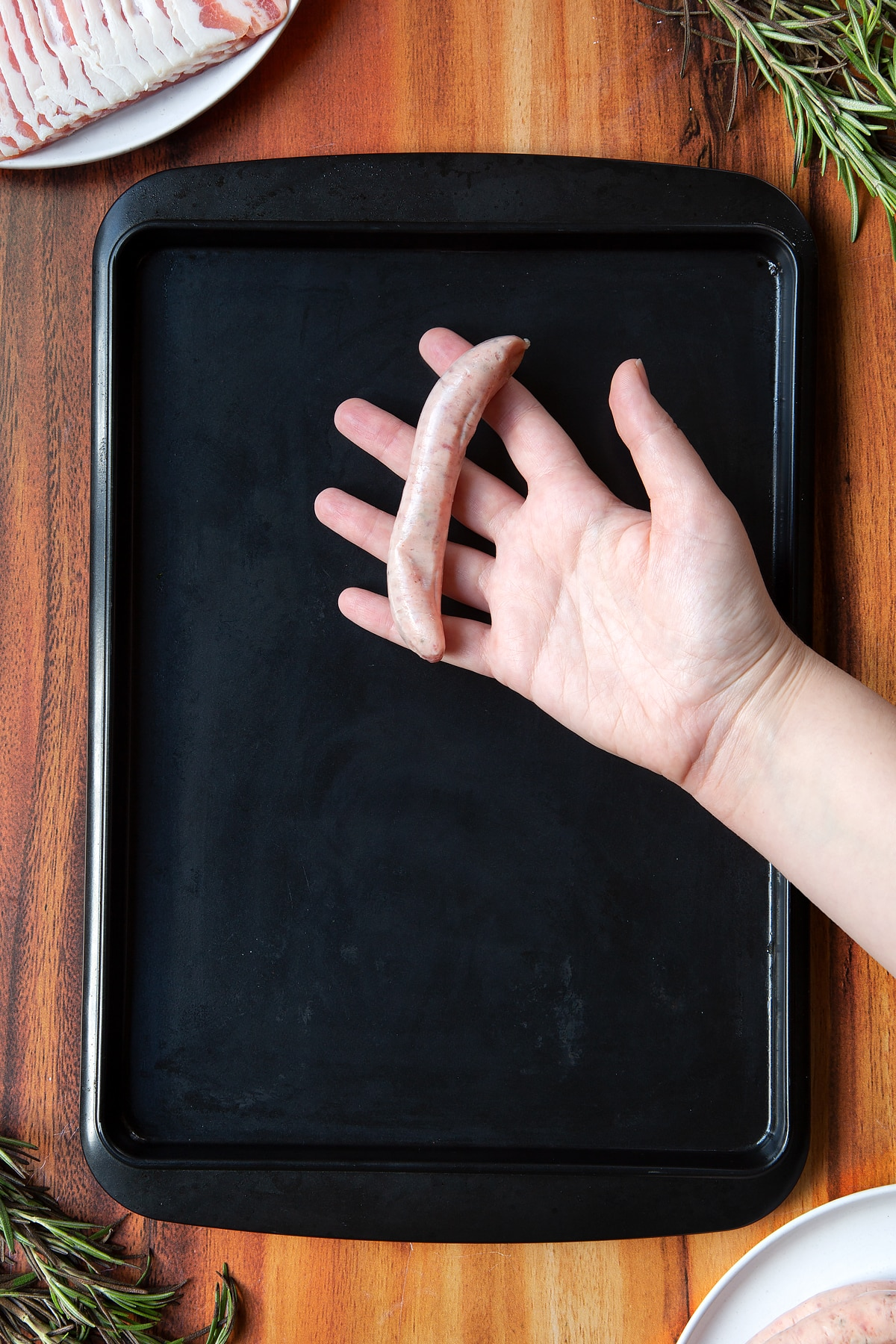 Overhead shot of a hand holding a sausage above black tray
