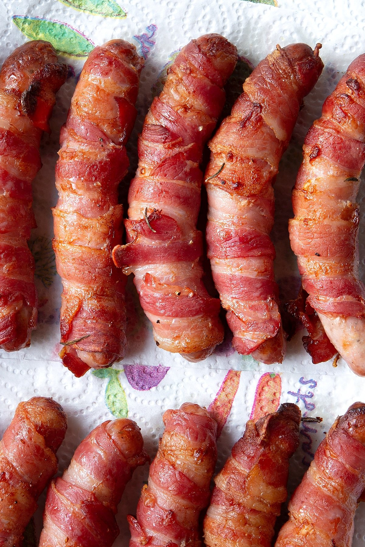 Close up overhead shot of the bacon wrapped sausages cooling on a paper towel.