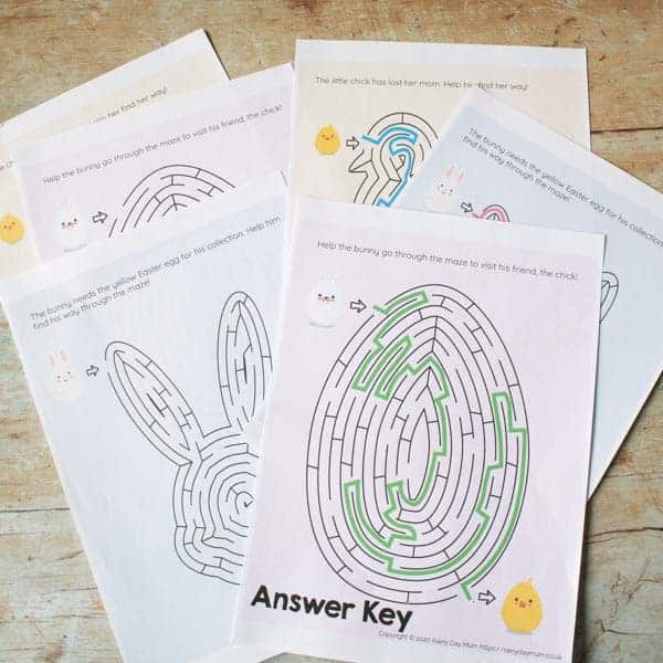 A collection of Easter-themed maze puzzles, printed on A4 paper, lying on a wooden backdrop.