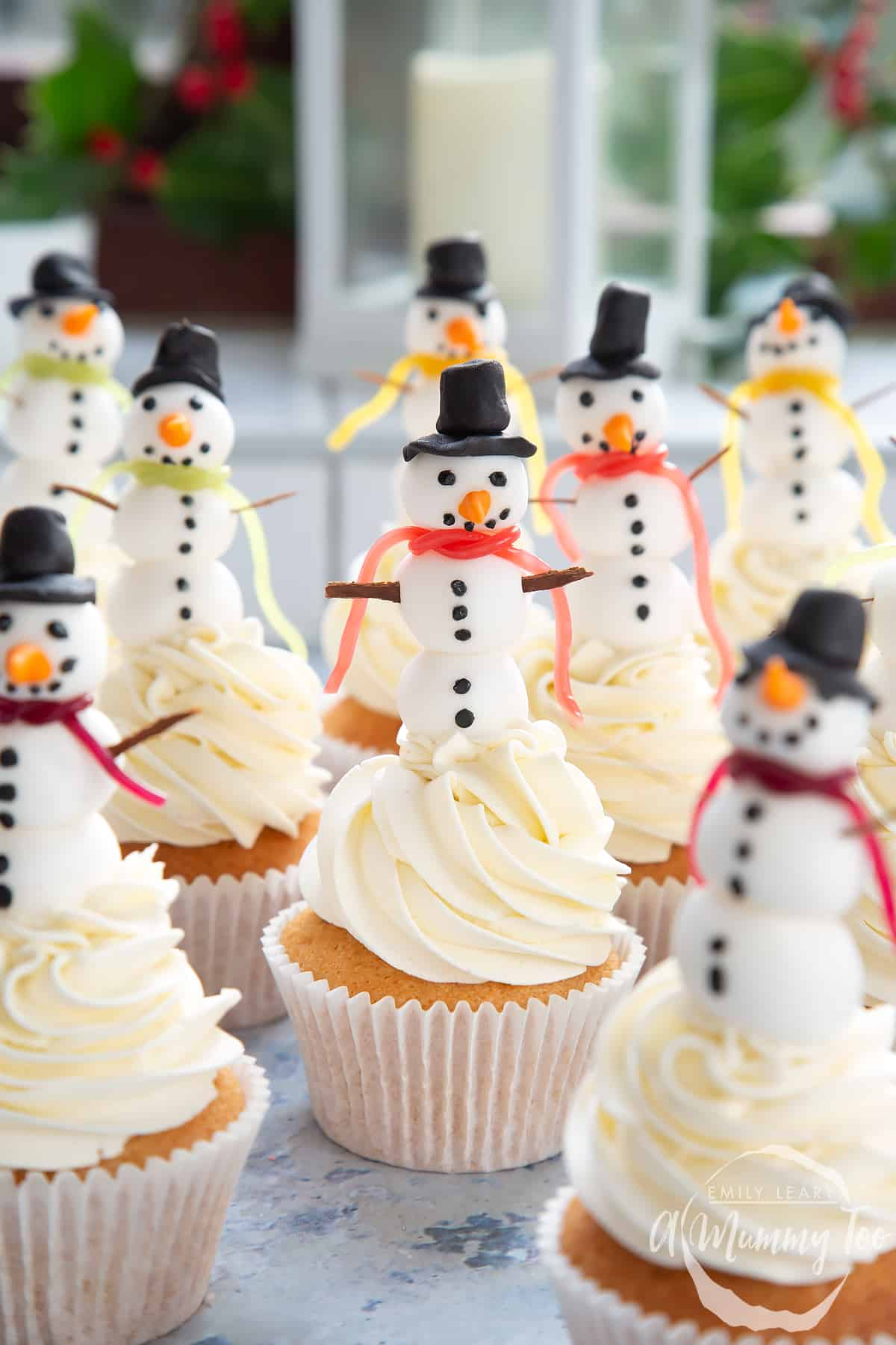 Multiple snowman cupcakes sat on a table with festive decorations in the background.