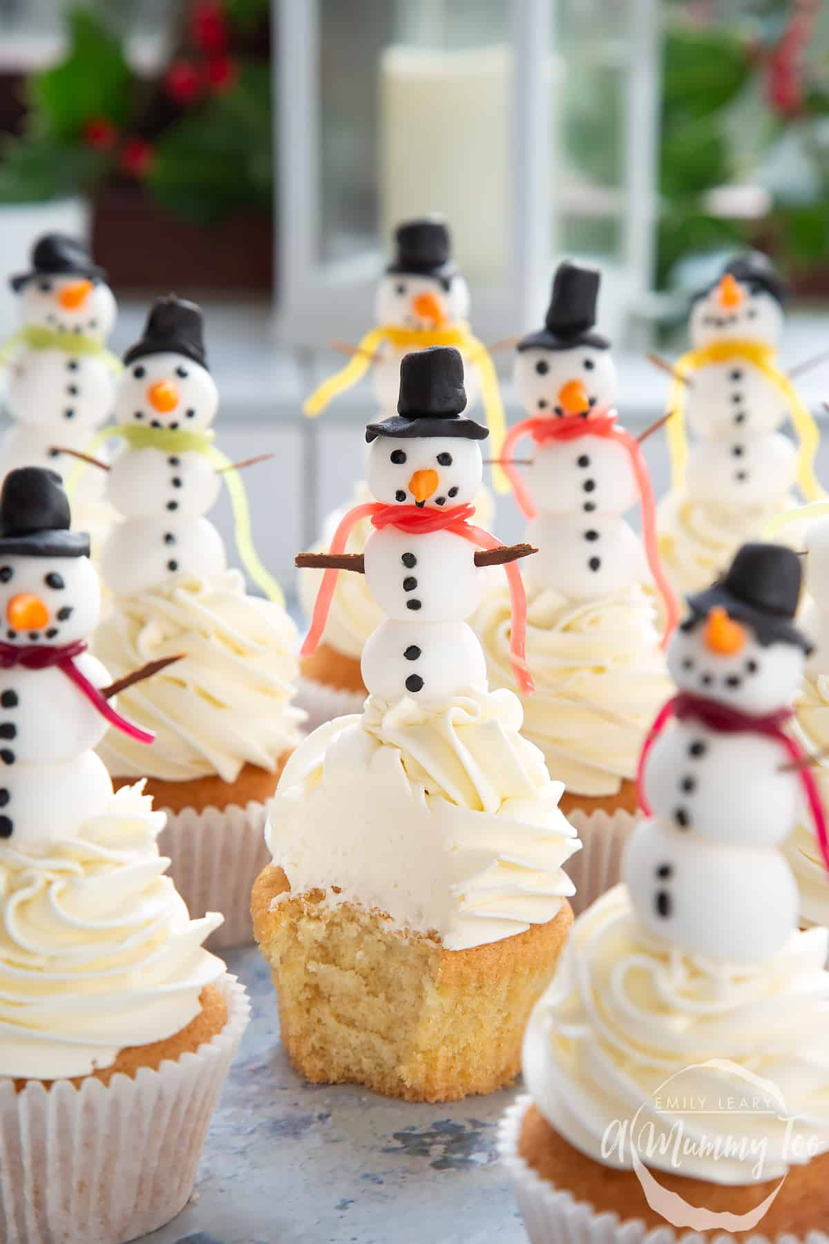 Multiple snowman cupcakes on a table with a festive background. The centered snowman cupcake has been unwrapped and a bite taken out.