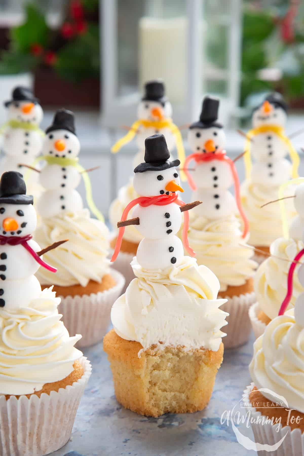 Multiple snowman cupcakes sat on a table. The centered snowman cupcake has been upwrapped and a bite has been taken out.