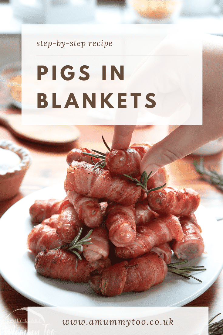 Front shot of a hand reaching in to grab a pig in blanket from the top of a stack build on a white plate. At the top of the image there's some text describing the image for Pinterest.