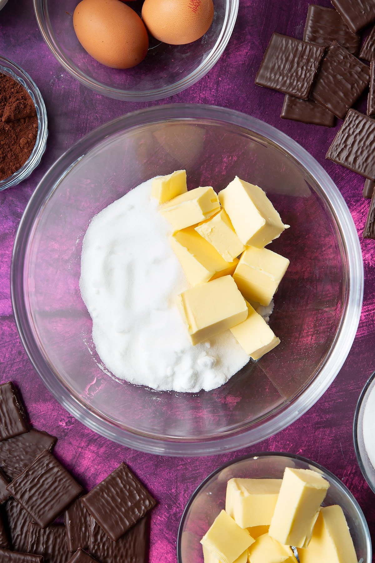 Sugar and butter in a glass mixing bowl. Ingredients to make After Eight cupcakes surround the bowl.