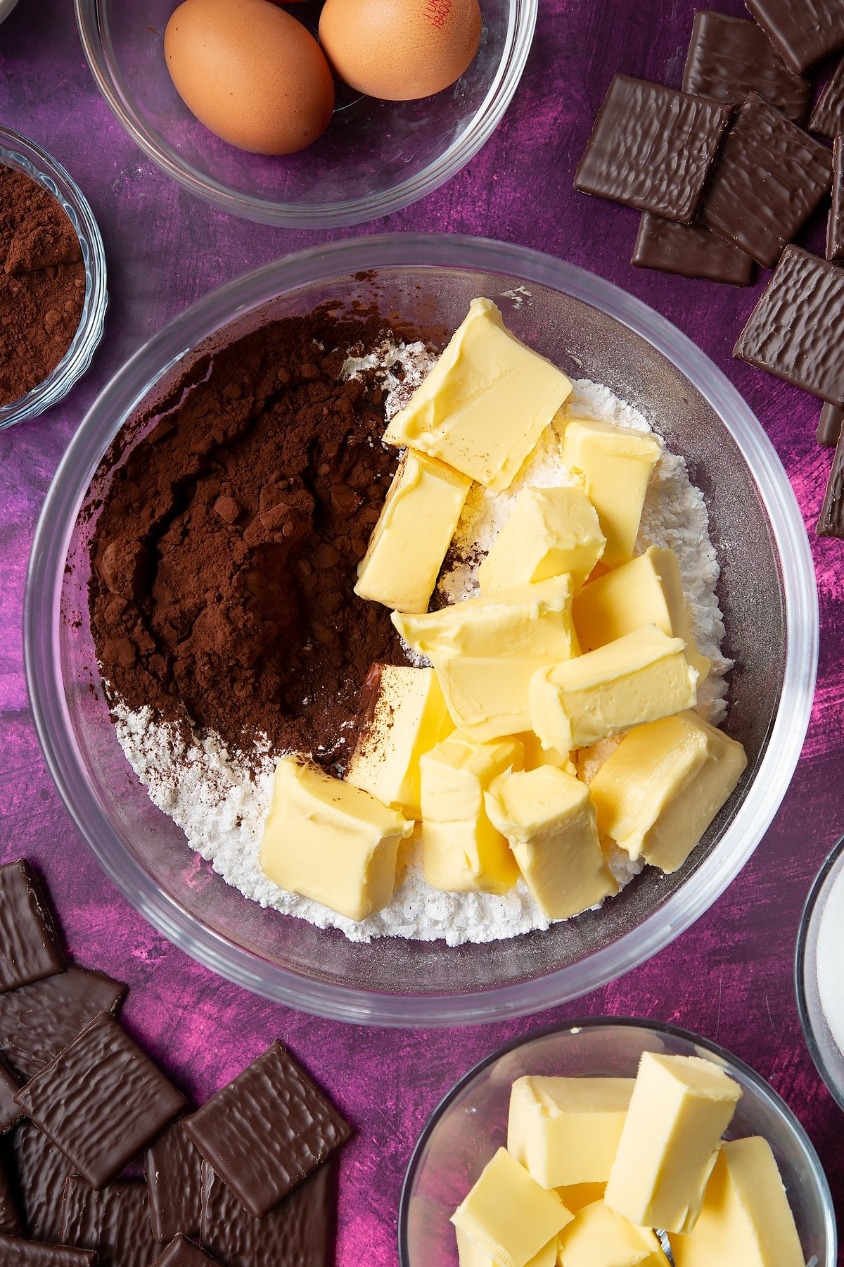 Icing sugar, butter and cocoa in a glass mixing bowl. Ingredients to make After Eight cupcakes surround the bowl.