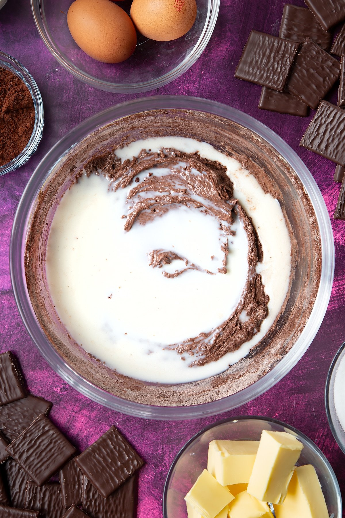 Sugar, butter, eggs, flour and cocoa mixed together in a glass mixing bowl with milk on top. Ingredients to make After Eight cupcakes surround the bowl.