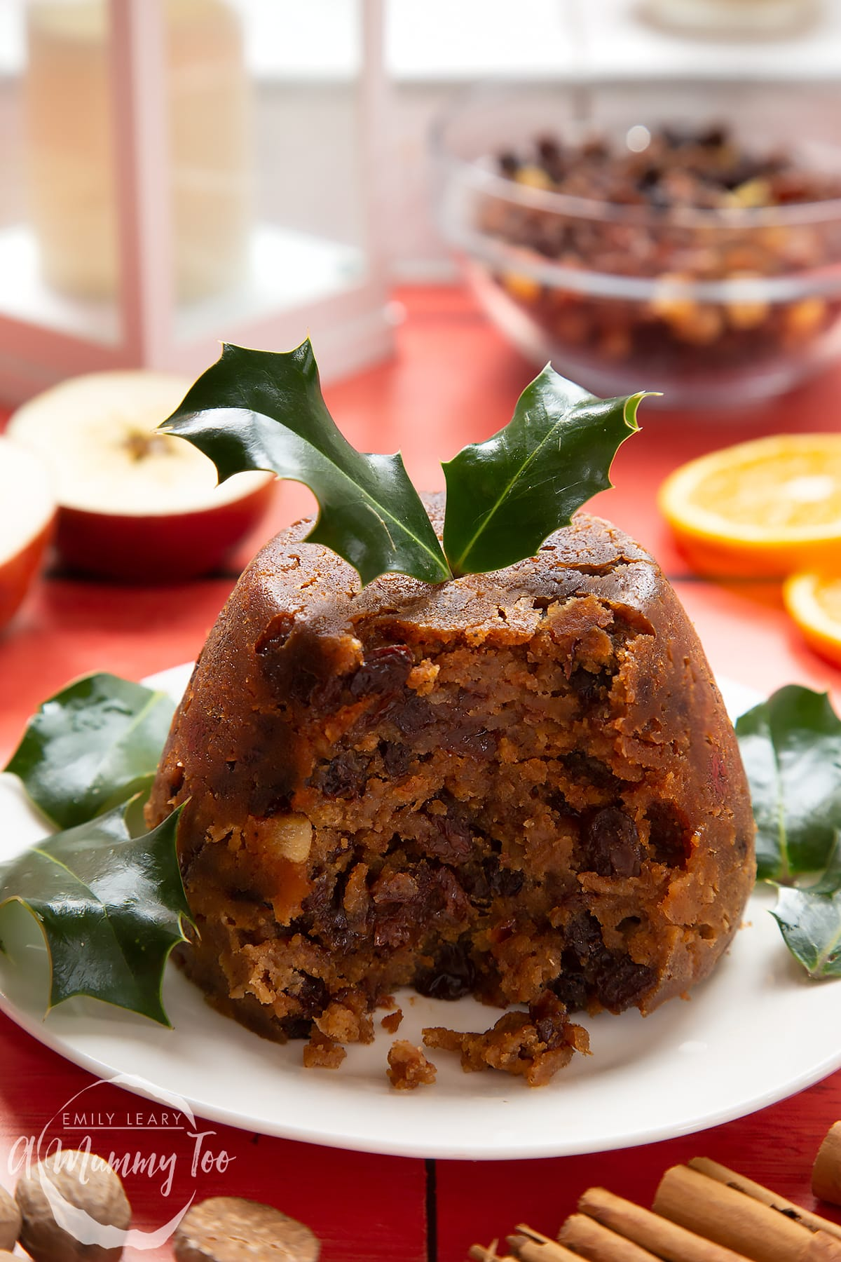 Front angle shot of half eaten Alcohol-free Christmas pudding served on a white plate with a mummy too logo in the lower-left corner