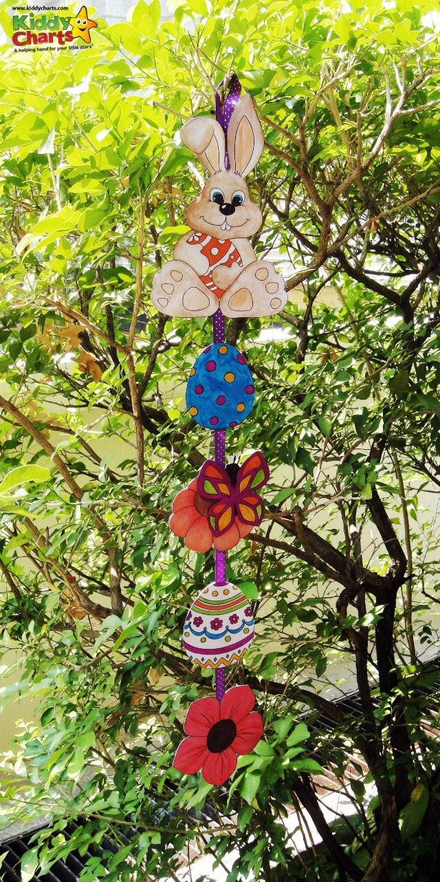 Coloured Easter images such as eggs, flowers and bunnies, cut up and strung on ribbon, hanging from a tree.