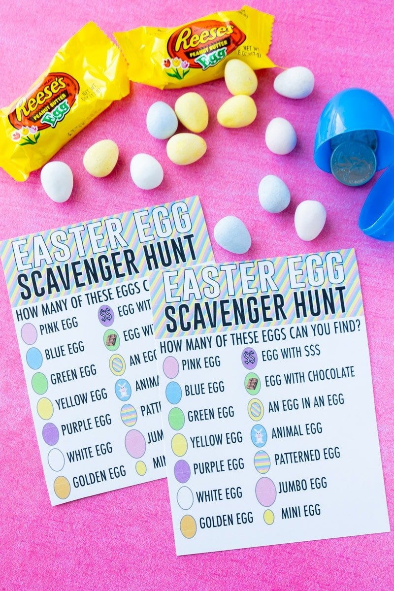 """Two Easter Egg scavenger hunt cards on a pinch surface surrounded by chocolate eggs. The cards challenge hunters to find various eggs such as """"blue egg"""", """"patterned egg"""" etc."""